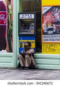 prague, czech - circa november 2015 - a poor man in front of an atm
