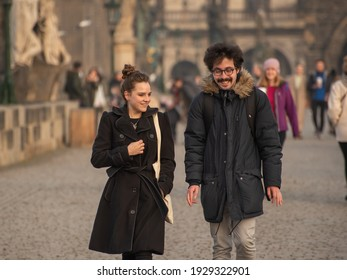 Prague, Czech Republic. 03-02-2021. Young couple smiling and having good fun on the Charles Bridge in the city center of Prague during winter with a beautiful sunset.