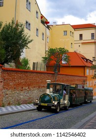 Prague / Czech Republic - 07 17 2017: a walking car in the form of an old green locomotive with two trailer cars carries tourists to the hill along a narrow street with a cobblestone pavement