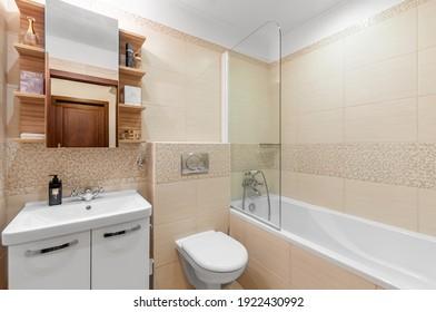 PRAGUE, THE CZECH REPUBLIC, 15.9.2020 - Luxury bathroom with sandstone decor and bathtub. White sink with mirror.