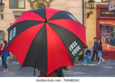 """PRAGUE, CZECH REPUBLIC - 15TH OCTOBER 2017: A man holding an umbrella in Pragues Old Town that says """"FREE TOUR"""" on it."""