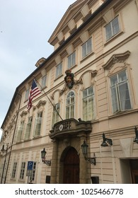 Prague, Czech Republic - 17 August 2017: Facade of the US Embassy in Prague. Seal of the United States and US Flag flapping in the wind above the carved archway. Outside the US Embassy in Prague.