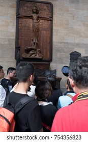 Prague, Czech Republic - 17 August 2017: Group of Asian tourists gather around a wooden carving of Christ on the Cross in side St Vitus Cathedral in Prague.