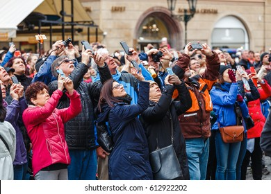 PRAGUE, CZECH REPUBLIC - 18 MARCH, 2017: A multinational large crowd of tourists photograph on smartphones and look up at the city's landmark