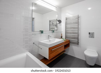 PRAGUE, THE CZECH REPUBLIC, 20.8.2020 -Luxury white marble interior of bathroom with bathtub, white sink and wooden furniture.