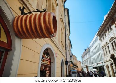Prague, Czech Republic, 27 June 2019: Cafe on street in old town in Prague, outside near enter cafe big symbol of tradition cooky (trdelnik)