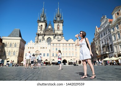 Prague, Czech Republic, 28 June 2019: Caucasian tourist woman holding and tasting tradition Czech sweet cookie (trdelnik) in the centre old town Prague on Tyn church background.