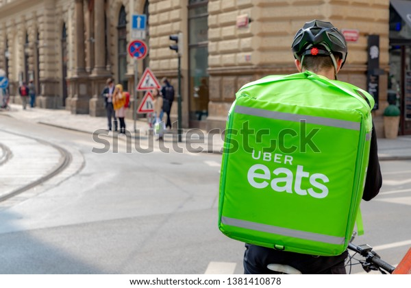 PRAGUE, THE CZECH REPUBLIC - April 10, 2019: Uber Eats is an International food delivery company, Cyclist carrying backpacks delivers food, You can order food from the restaurant and eat it at home.