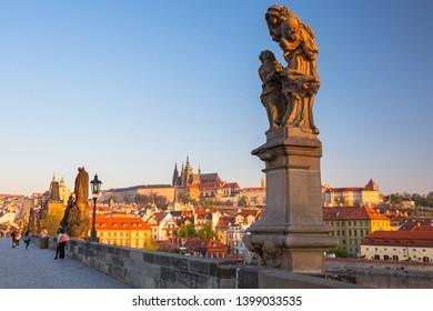 Prague, Czech Republic - April 20, 2019: People on the Charles bridge in Prague at sunrise, Czech Republic