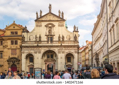 Prague, Czech Republic - April 2019: Outdoor sunny view of crowd of tourist in front Church of St. Salvator, beautiful Cathoric Church located in old town opposite Gate tower of Charles Bridge.