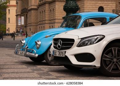 PRAGUE, CZECH REPUBLIC - APRIL 21, 2017: A small blue vintage Volkswagen Beetle car next to a big white Mercedes, parked in front of the Rudolfinum concert hall