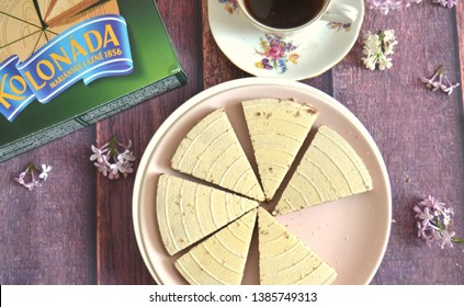 Prague / Czech Republic - April 30 2019: Original czech Kolonada spa waffer triangles:  Chocolate filled biscuits by Opavia, original wrap box, vintage cup of tea, lilac blossoms