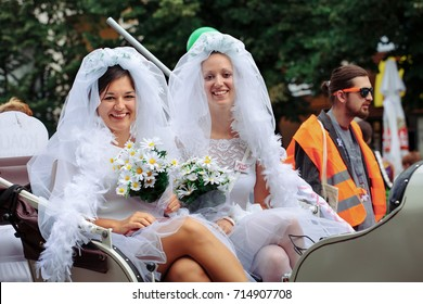 PRAGUE, CZECH REPUBLIC – AUGUST 12, 2017: two women dressed as brides sit in a carriage at Gay Pride parade. Lesbian wedding couple represents lgbt, gay, same-sex marriage, equal rights concept.