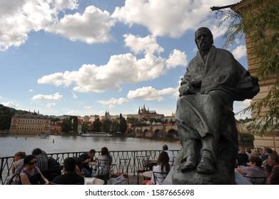 PRAGUE/ CZECH REPUBLIC  - AUGUST 16 2011:  Outdoor dining at Restaurant Lavka beneath the statue of Bedrich Smetana near Vltava River overlooking Charles Bridge and Prague Castle.