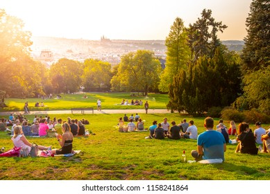 PRAGUE, CZECH REPUBLIC - AUGUST 17, 2018: Sunset in Rieger Gardens, Riegrovy sady, in Prague. Many people sitting in the grass and enjoying sunny summer evening and lookout of Prague historical city