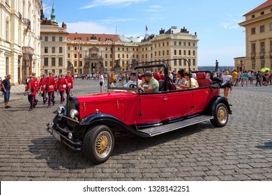PRAGUE, CZECH REPUBLIC - AUGUST 18, 2018: Tourists in retro car visit on Hradcany Square. Fragment of the solemn ceremony of changing the honor guard.