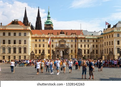PRAGUE, CZECH REPUBLIC - AUGUST 18, 2018: Tourists walking in front Gate of the Giants on Hradcany Square. Fragment of the solemn ceremony of changing the honor guard.