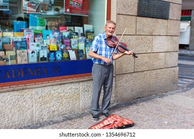 PRAGUE, CZECH REPUBLIC - AUGUST 19, 2017. A street musician playing the violin on the corner of the street. Old man makes money by busking.