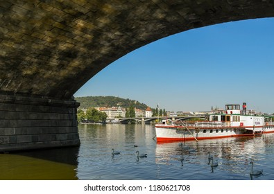 PRAGUE, CZECH REPUBLIC - AUGUST 2018: Sightseeing river cruise boat on the River Vltava, which runs through the centre of Prague. The view is framed by the arch of a bridge.