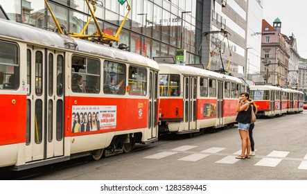 PRAGUE, CZECH REPUBLIC - AUGUST 2018: Trams queuing in Prague city centre blocking two people waiting to cross the street on a pedestrian crossing.