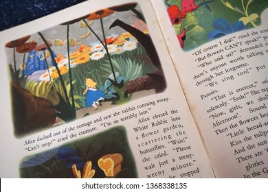 Prague / Czech republic - August 21 2018: Vintage Disney's illustrated Alice in Wonderland open book showing extract of the text and pictures