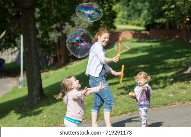 Prague, Czech Republic - August 21, 2017: mom with two children play with soap bubbles at Letna park