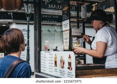 Prague, Czech Republic - August 23, 2018: Tourists buying Trdelnik, a sweet pastry that is popular amongst locals and tourists and is sold in many European countries, mostly in the Czech Republic.
