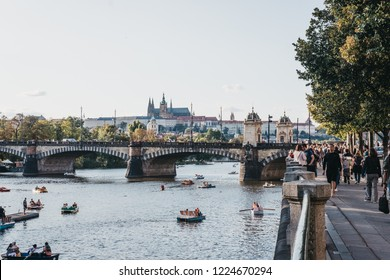 Prague, Czech Republic - August 23, 2018: Paddle boats on Vltava river in Prague on a sunny summer day, people walk on the riverbank. Vltava is the longest river within the Czech Republic.