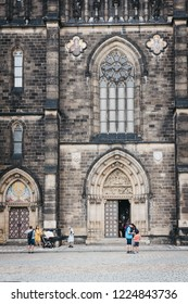 Prague, Czech Republic - August 23, 2018:  People walking in front of Saint Peter and Paul Basilica, a neo-Gothic church in Vysehrad fortress in Prague, Czech Republic.