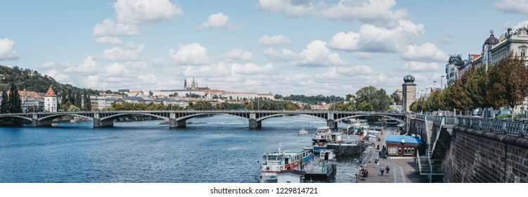 Prague, Czech Republic - August 23, 2018: Vltava river in Prague on a sunny summer day, people walk on the riverbank. Vltava is the longest river within the Czech Republic.