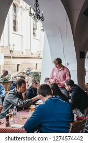 Prague, Czech Republic - August 23, 2018: People drinking beer at the outdoor tables of a Czech restaurant in Prague. Beer is a large part of Czech culture.