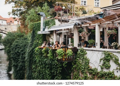 Prague, Czech Republic - August 23, 2018: People drinking beer at the outdoor tables of Velkopřevorský Mlýn restaurant in Mala Strana, Prague. Beer is a large part of Czech culture.