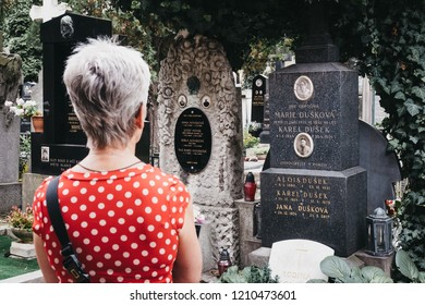 Prague, Czech Republic - August 26, 2018: Woman looks at the thombstones in Vysehrad cemetery in Prague. Vysehrad cemetery is the final resting place of many famous composers, artists and politicians.