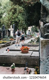 Prague, Czech Republic - August 26, 2018: Tourists walking in Vysehrad cemetery in Prague. Vysehrad cemetery is the final resting place of many famous composers, artists and politicians.