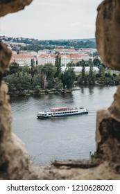 Prague, Czech Republic - August 26, 2018: Tour boat on Vltava river in Prague, view from Vysehrad Castle. Vltava is the longest river within the Czech Republic.