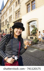 PRAGUE, CZECH REPUBLIC - AUGUST 30 : Asian woman posing with Czechia actor  acting Magic show on street for show people and travelers near Charles Bridge on August 30, 2017 in Prague, Czech Republic