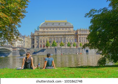 PRAGUE CZECH REPUBLIC - AUGUST 31; Vltava River view to National Theater  tourists enjoying outdoors little boats and silhouetted on embankment enjoying outdoors  August 31 2017 Prague Czech Republic