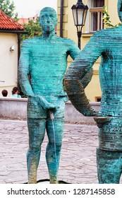 "PRAGUE, CZECH REPUBLIC - AUGUST 5, 2018: Sculpture ""Peeing Statues"" by David Cerny and the Museum of Franz Kafka in the yard of Hergetova Cihelna, Prague."