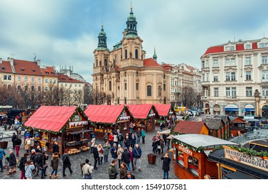 PRAGUE, CZECH REPUBLIC - DECEMBER 10, 2015: People walking among wooden stalls with souvenirs and traditional food at Christmas market taking place each year on December on Old Town Square of Prague.