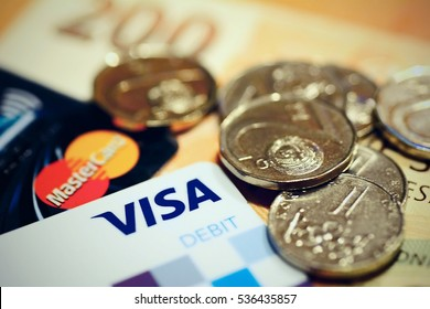 PRAGUE, CZECH REPUBLIC - DECEMBER 12, 2016: Conceptual shot with czech currency coins and bills put on the VISA and MasterCard payment debit cards.