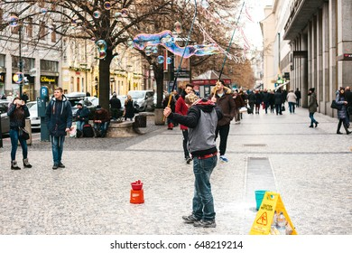 Prague, Czech Republic, December 24, 2016: The artist shows a performance with soap bubbles for tourists on the street in Prague. Entertainment of tourists in Christmas Europe. Street show.