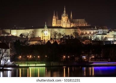 Prague, Czech Republic  - December 5, 2016 : Long exposure photography of  Prague castle, beautiful lighting with Vltava river in foreground
