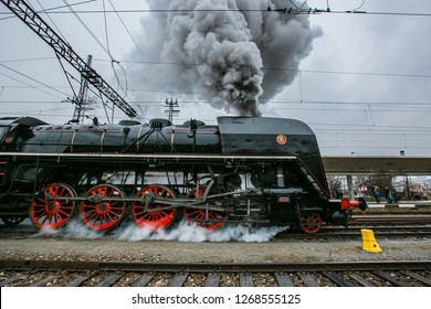Prague, Czech Republic / Europe - December 15 2018: Old black steam engine, red wheels, made in 1948 running on railway track at Smichov train station, belching out thick grey steam, snowing