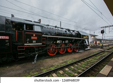 Prague, Czech Republic / Europe - December 15 2018: Old black steam engine with tender, red wheels, made in 1948 on railway track at Smichov train station belching out thick grey steam, snowing