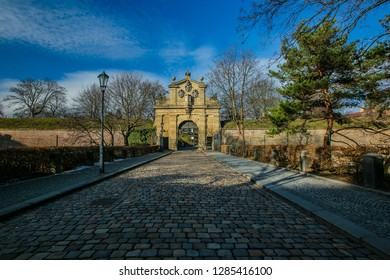 Prague, Czech Republic / Europe - January 15 2019: Stone Leopolds gate at Vysehrad is a Baroque gate from Prague fortification built in 17th century, cobble stone street, sunny day, blue sky, trees