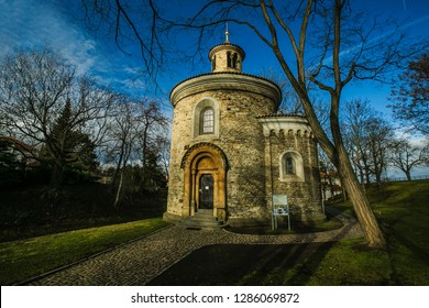 Prague, Czech Republic / Europe - January 16 2019: Medieval rotunda of saint Martin built in 11th century made of stone standing at Vysehrad, green grass, park with trees, sunny day, blue sky