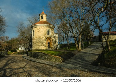 Prague, Czech Republic / Europe - January 16 2019: Medieval rotunda of saint Martin built in 11th century made of stone standing at Vysehrad, cobble stone street, trees, sunny day, blue sky