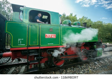 Prague, Czech Republic / Europe - September 15 2018: Green and red steam engine Beeska standing on railway track belching out white smoke, train driver in the window, sunny day, blue sky, clouds