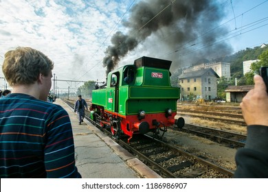 Prague, Czech Republic / Europe - September 15 2018: Green and red steam engine Beeska coming to train station Smichov belching out black smoke, people standing on platform taking pictures, blue sky