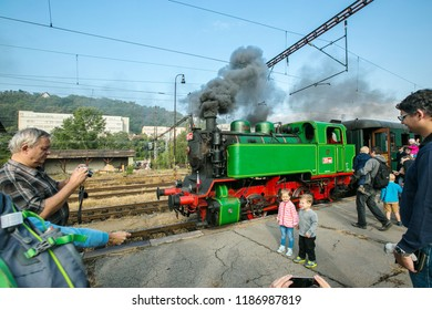 Prague, Czech Republic / Europe - September 15 2018: Green and red steam engine Beeska standing on railway track belching out black smoke, people taking pictures, children standing on platform
